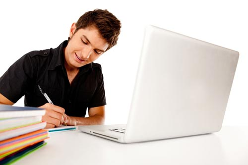 Happy male student with a laptop and notebooks
