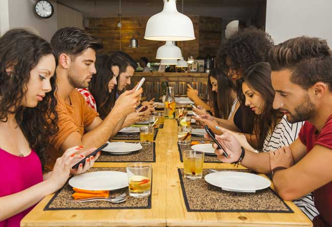 Group of friends at a restaurant occupied with cell phones