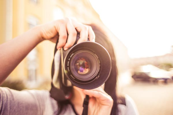 Girl taking photograph with DSLR camera