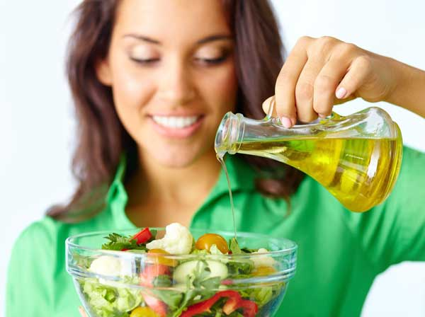 Young woman pouring oil onto salad