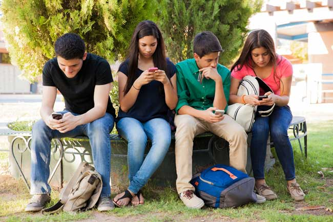 Teenagers on cell phones ignoring each other