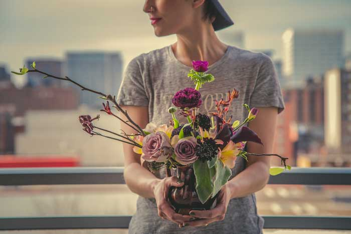 Woman holding flower arrangement