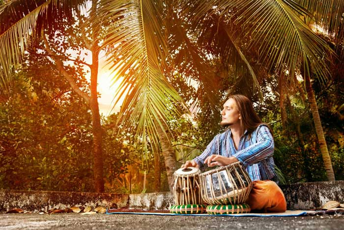 Man playing traditional Indian tabla at sunset