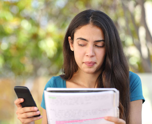 Teenage student looking sideways at mobile phone while studying