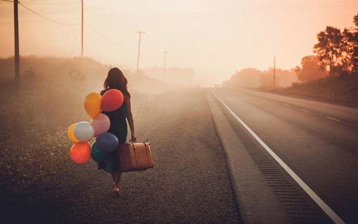 Girl carrying balloons and walking down a long road
