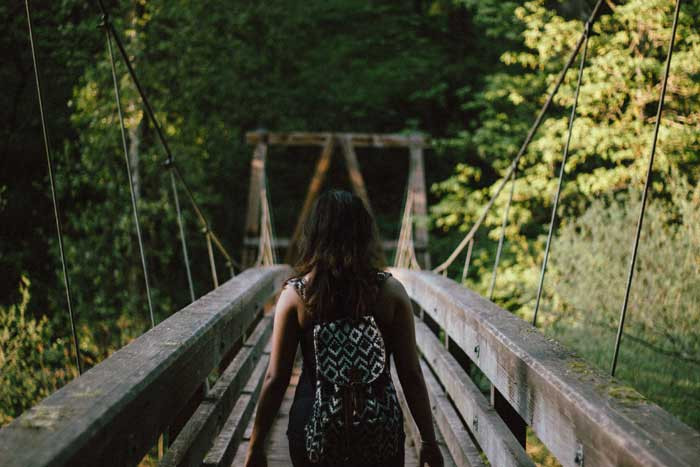 Girl walking on bridge into the unknown