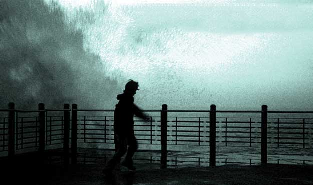 Man standing near railing as waves wash up