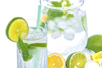 Chilled water in glass and jug with ice, lime and mint