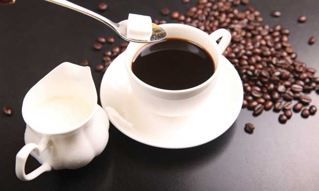 Sugar cube being dropped into black coffee