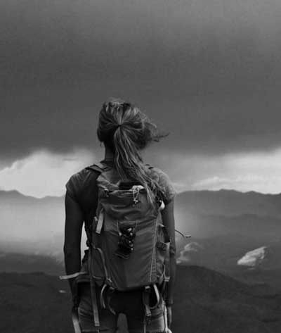 Girl with backpack looking at dark clouds in the sky