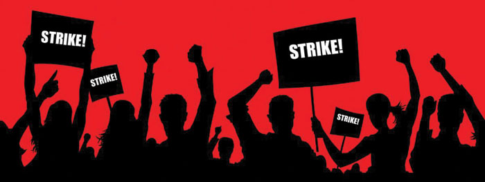 Silhouettes of people holding strike signs