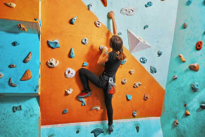 Young woman climbing up practice wall in gym