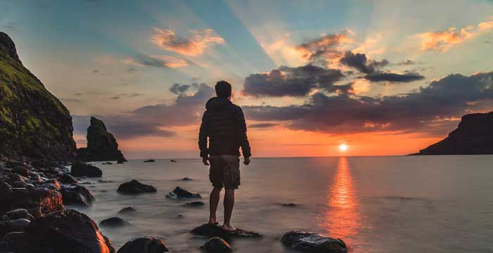 Boy standing on rocks in sea looking at sunset