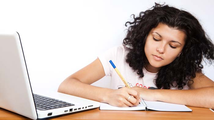 Girl writing in notebook near laptop