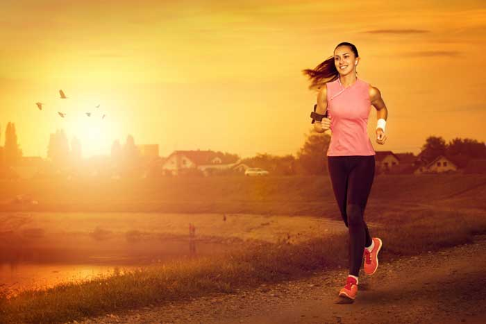 Young woman jogging outdoors at sunset