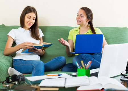 Teenage girls studying together with books and laptops
