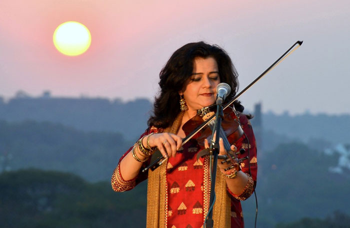 Sunita Bhuyan playing the violin at sunset