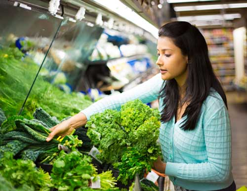 Young girl choosing leafy green vegetables