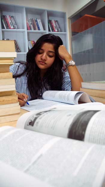 Girl studying for exams with open books in front of her