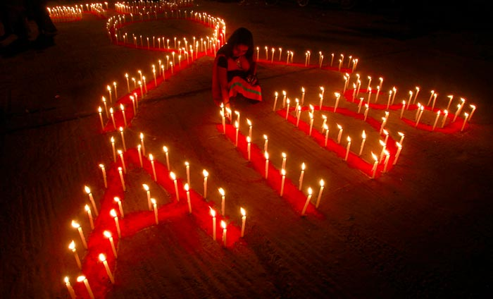 Candles lit up in the shape of the AIDS symbol
