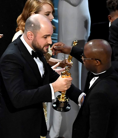 Jordan Horowitz handing the Oscar trophy to Barry Jenkins