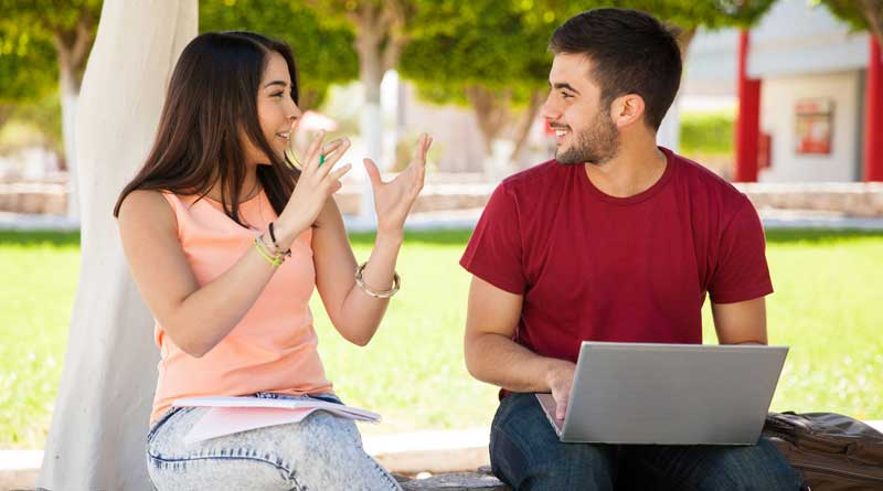 Teen girl talking to a guy with a laptop