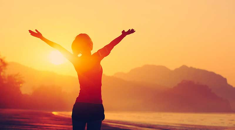 Woman raising hands towards sunset