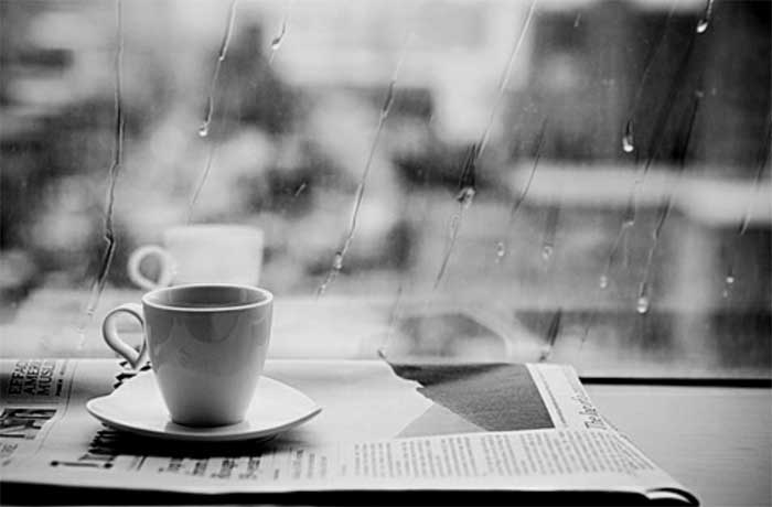 Coffee cup and newspaper near a window with rain falling on it