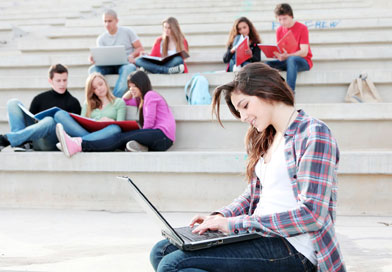 Student on university campus with laptop