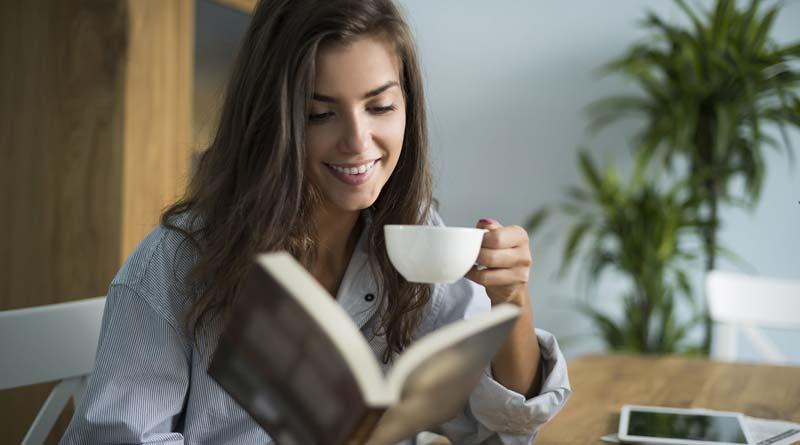 Young woman reading a book while drinking coffee