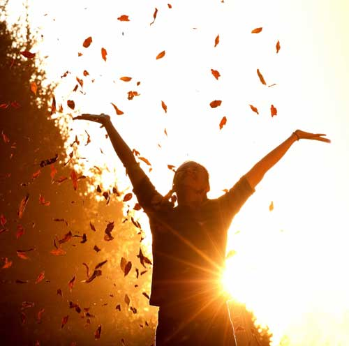 Girl throwing leaves into the air at sunset