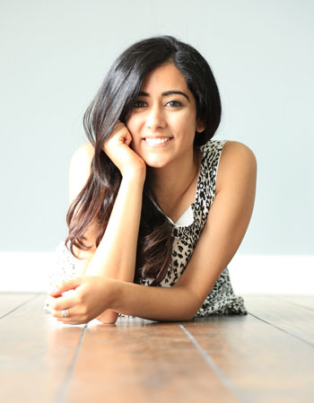 Jonita Gandhi leaning on an arm and smiling