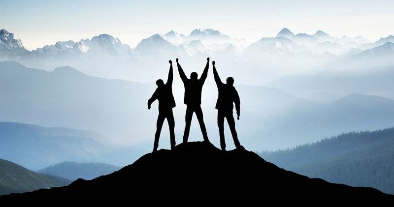 Three human silhouettes on a mountaintop