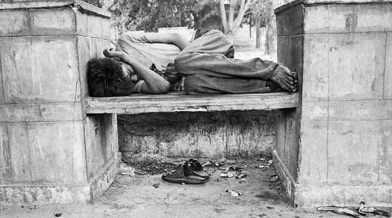 Street child sleeping on a street bench