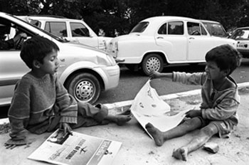 Two street children reading the newspapers on the footpath
