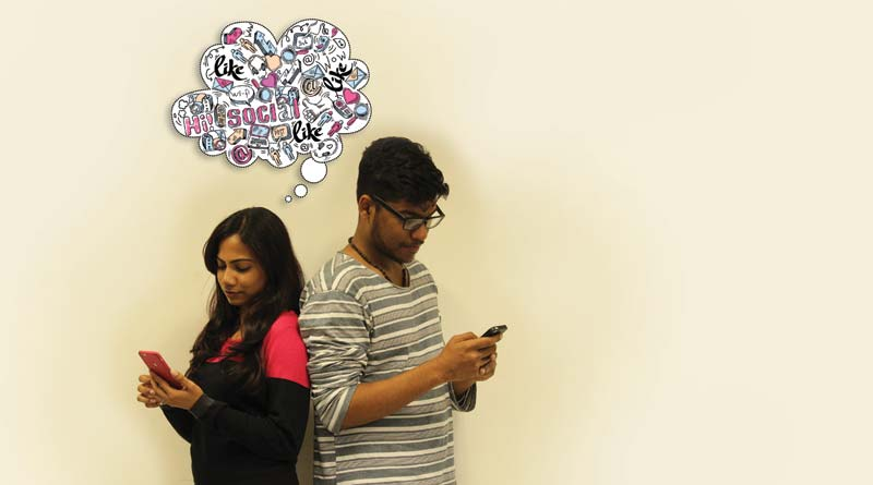 A boy and girl busy on their smartphones and ignoring one another