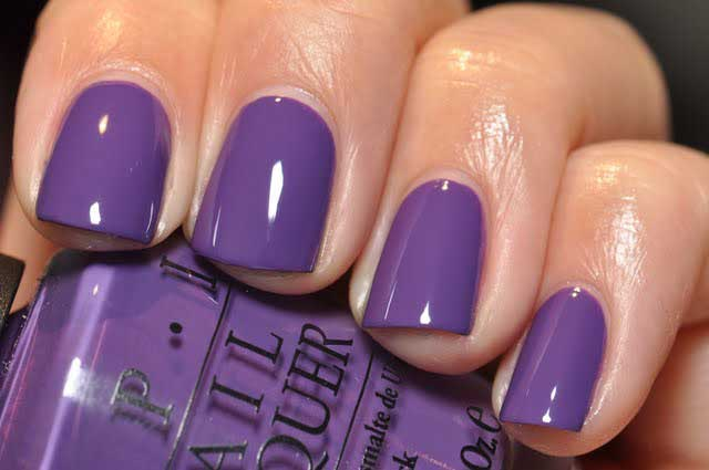 Nails painted in ultra violet shade holding a nail polish bottle