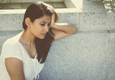 Sad and depressed young woman leaning against a wall