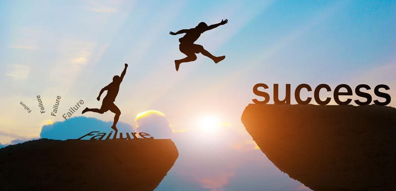 Man jumping from cliff with failure on it to cliff with success on it