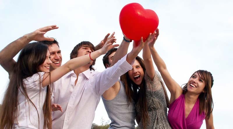 A group of happy girls and guys holding onto heart-shaped red balloon