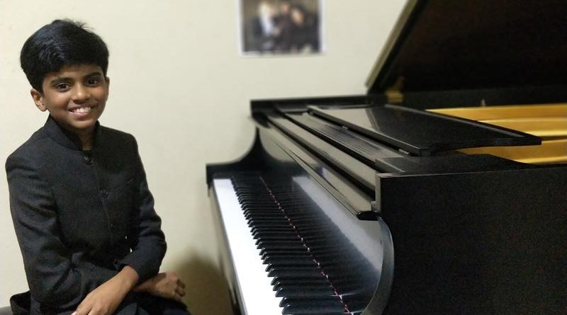 Lydian Nadhaswaram sitting at a baby grand piano
