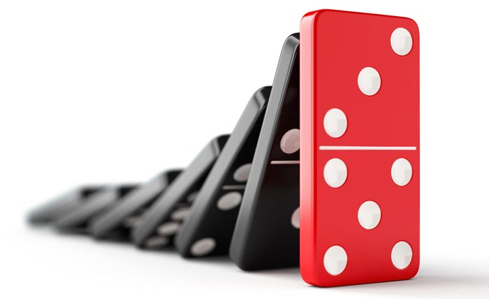 Falling black dominoes about to hit red domino