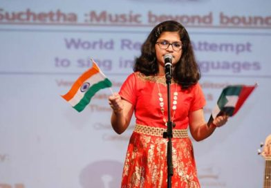 Sumitha Satish on stage singing while holding the flags of India and UAE
