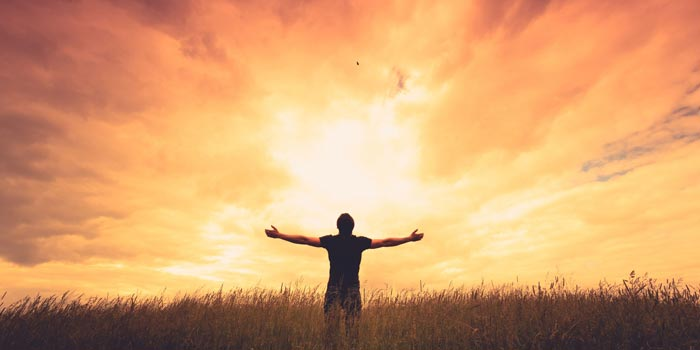Man standing in a field at sunset and raising his arms to the sky