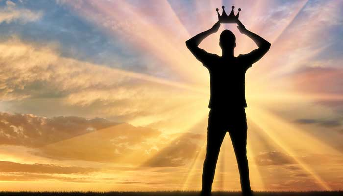 Silhouette of man placing crown on his own head