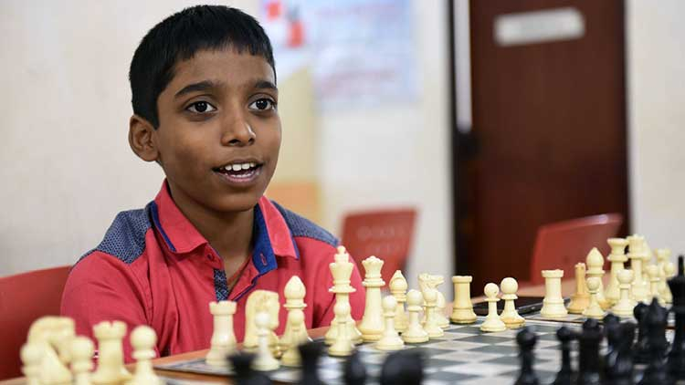 Praggu sitting in front of a chess board
