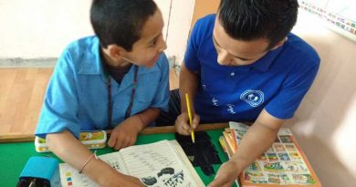 A special needs student being taught by a male teacher