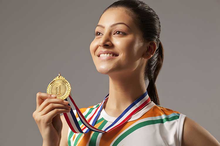 Young woman wearing Indian colours holding up a gold medal with number one engraved on it.