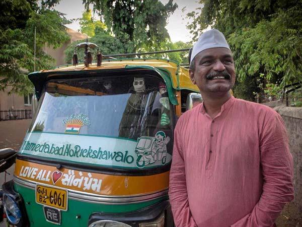 Udaybhai standing near his rickshaw