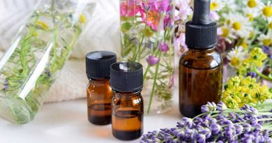 Essential oil bottles surrounded by herbs and flowers